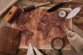 pohled na starou mapu světa blízko dalekohledu, špičky a kompasu na dřevěné ploše