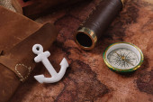 Photo white anchor near leather copy book, compass and telescope on old world map