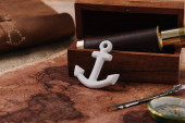 Photo white anchor near open wooden box with telescope on world map