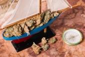 Dekorationsschiff mit trockenen Pflanzenklumpen in der Nähe des Kompasses auf der alten Weltkarte