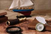 loď, dalekohled, zvětšovací sklo, kožené kopírovací knížka a špičky na staré mapě a Hesejan