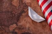 Fényképek fehér papír csónak közelében amerikai nemzeti zászló az ókori világtérképen
