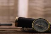 blízký pohled na kompas u teleskopu a lana na dřevěném stole