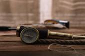 kompas v blízkosti dalekohledu a lanového kabelu na hnědém dřevěném stole