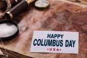 Fotografia carta con felice Columbus Day iscrizione vicino bussola e lente di ingrandimento sulla mappa del vecchio mondo
