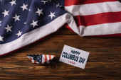 top view of card with happy Columbus Day inscription near paper boat on wooden surface with American national flag