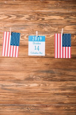 Calendar paper sheet with 14 October date between American national flags on wooden surface stock vector