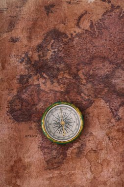 top view of compass on ancient world map