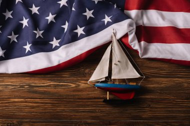 Top view of leather crafted ship on wooden surface with American national flag stock vector