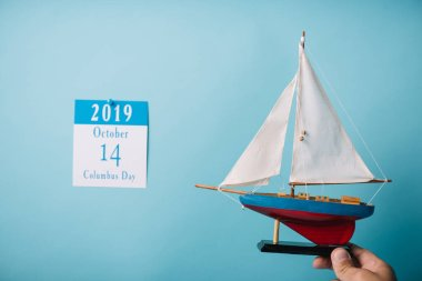 cropped view of man holding crafted ship near paper calendar with Columbus Day inscription isolated on blue