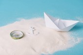 Photo sand with paper boat, compass and anchor on blue background