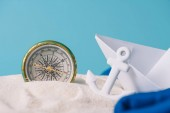 Photo white sand with paper boat, anchor and compass isolated on blue