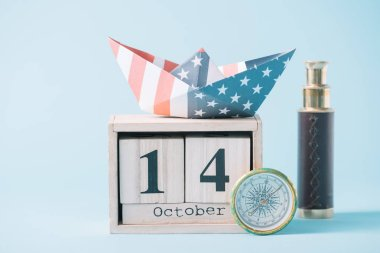 Paper boat with American flag pattern on wooden calendar with October 14 date near compass and telescope on blue background stock vector