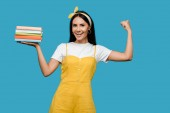 glückliche Frau mit Stirnband, Bücher in der Hand und gestikulierend isoliert auf blauem Grund
