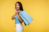 vzrušená žena držící nákupní tašky izolovaná na oranžovém