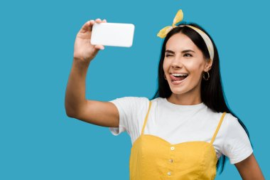 young woman taking selfie on smartphone while showing tongue isolated on blue