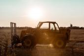 sunlight on tractor near wheat field in evening