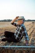 contadino autonomo seduto su balla di fieno e toccando cappello di paglia