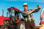 selective focus of happy self-employed farmer taking selfie near tractor