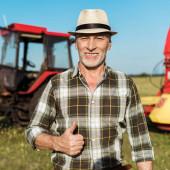vidám gazda szalma kalap mutató hüvelykujját a traktor közelében