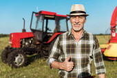 happy farmer in straw hat showing thumb up near tractor