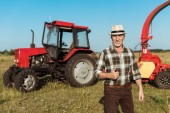 happy self-employed farmer in straw hat showing thumb up near tractor