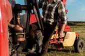selektivní zaměření samostatně výdělečně hospodachovného zemědělce stojícího poblíž moderního traktoru