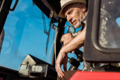 low angle view of senior farmer touching steering wheel in tractor