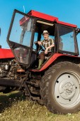 senior self-employed farmer in straw hat driving tractor