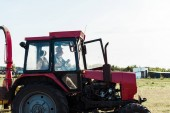 bearded senior farmer in straw hat driving tractor