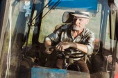 selective focus of cheerful self-employed farmer smiling while driving tractor