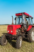 senior farmer driving red tractor in wheat field