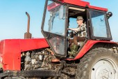 senior farmer driving modern and red tractor