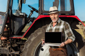 happy farmer in straw hat holding laptop with blank screen near tractor