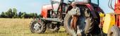 panoramatický záběr farmáře v slaměném klobouku s použitím notebooku u traktoru