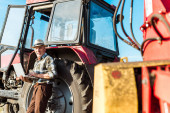 selective focus of happy farmer in straw hat using laptop near tractor