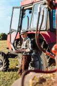selektivní zaměření zemědělce na slaměný klobouk s použitím přenosného počítače v blízkosti traktoru