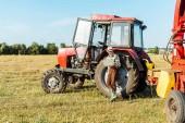 vousatý zemědělec v slamáku s použitím notebooku u traktoru