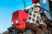 vyšší zemědělec v slaměném klobouku držící digitální tablet v blízkosti červeného traktoru