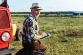 happy farmer in straw hat using digital tablet near red tractor