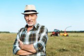 happy senior farmer standing with crossed arms in field