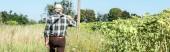 panoramic shot of self-employed man holding rack near green field