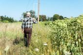 back view self-employed man holding rack near green field