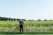 senior autonomo agricoltore toccando cappello di paglia e in piedi con la mano sullanca in campo