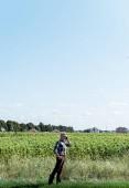 samostatně výdělečně zaměstnaný farmář, který mluví na telefonu, zatímco stojí s rukou na boku