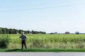 bearded self-employed farmer talking on smartphone in field