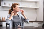 Frau mit süßer Allergie isst rosa Dessert, während sie sich am Hals kratzt