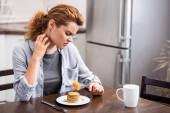 attraktive Frau mit Allergie kratzt Hals, während sie Gabel mit Pfannkuchen hält