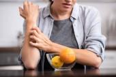abgeschnittene Ansicht einer Frau, die Hand an Glasschale mit Früchten kratzt