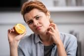 Verärgerte Frau mit halber Orange am Hals